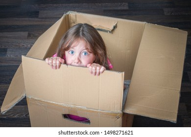 A scared girl peeks out of a cardboard box. The child is hiding from his parents in a mail box. The baby hid and is afraid of punishment.