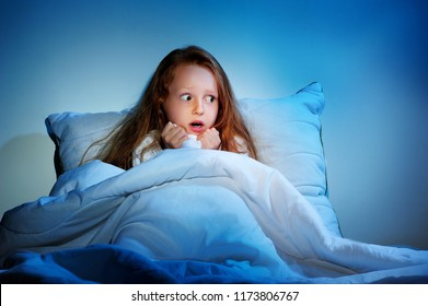 Scared girl staying sleepless in her bed