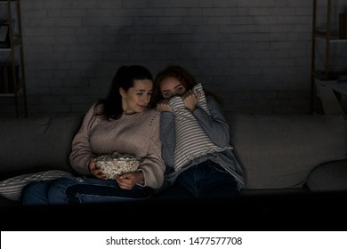 Scared girls watching horror movie on tv sitting on couch at home, late in the evening