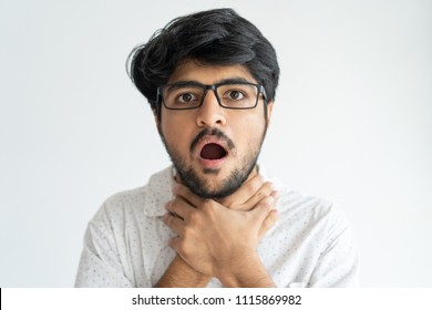 Scared Indian man keeping mouth open and choking himself. Shocked young man with beard making suffocating gesture and looking at camera. Cannot breath concept
