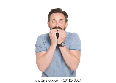 So scared. Intimidated bearded man biting his nails in panic while looking at you with the eyes full of anxiety