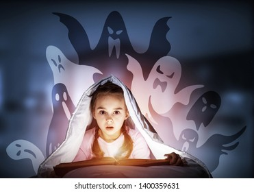 Scared kid with reading book under blanket. Afraid girl lying in bed at home. Child reading scary stories. Girl in pajamas and imaginary ghosts back on night sky. Bright light shining from open book.