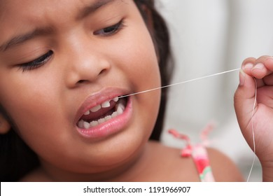 Scared little girl about to pull out her own front milk tooth