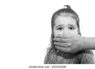 Scared little girl with an adult man's hand covering her mouth for any purpose