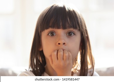 Scared little girl look at camera biting nails worrying about something, frightened small preschooler kid rounding eyes covering mouth, stressed child feel terrified or afraid left alone at home