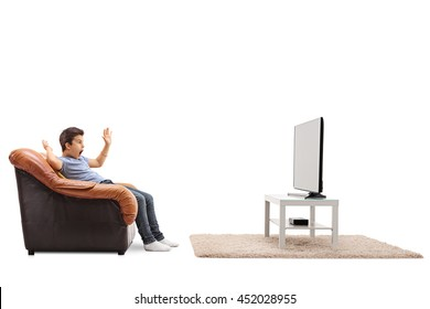 Scared little kid watching television seated on an armchair isolated on white background