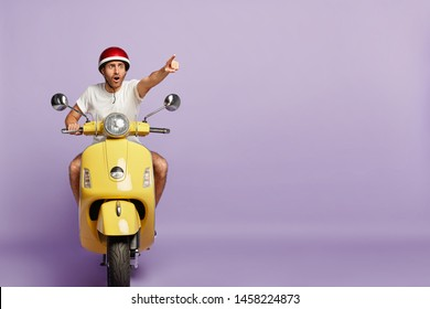 Scared man drives fast yellow scooter, wears protective helmet and white t shirt, points index finger in distance, notices scarying scene on road, poses against purple wall, blank copy space. Driving
