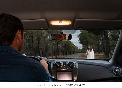 Scared man driving his car on a forest road and looking at a female ghost through the front windshield. Halloween nightmare. Halloween horror scene.