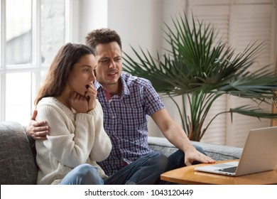 Scared man embracing shocked woman watching thrilling horror film or scary movie on laptop together, young couple feeling frightened and confused looking at computer screen sitting on sofa at home