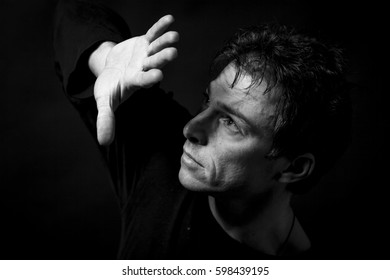 Scared man low key portrait, with a raised arm, as a sign of protection and confusion