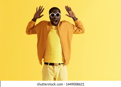 Scared man in sunglasses holding hands up on yellow background. Portrait of shocked black male model with afraid face expression in sunglasses and colorful clothes at studio