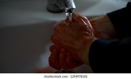 Scared man washing hands in sink after homicide, manslaughter, jealousy murder