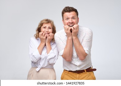 Scared man and woman biting their nails feeling stressed and surprised. Concept of deadline at work. Mother and son being impressed with news.