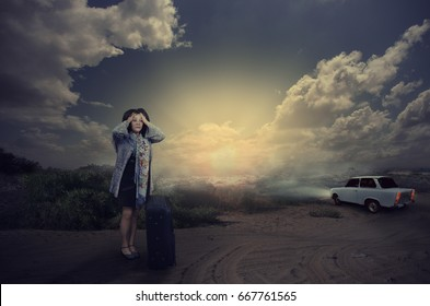 Scared mature woman with black suitcase standing in dark desert road. Terrified woman wearing cardigan holds her head with hands. White car drives away. Dramatic clouds in the dark sky.Horizontal shot