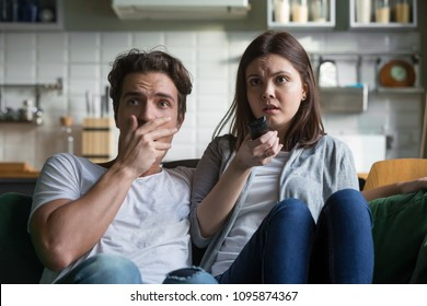 Scared millennial couple watching horror movie on tv holding remote control at home, frightened young man and woman feeling fear or surprise during thrilling scary film moment sitting on sofa at home