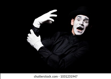 scared mime with hand monster looking at camera isolated on black