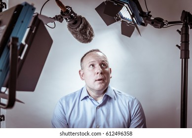 Scared and nervous man under video lights and microphone about to be interviewed on camera.