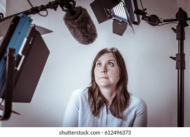 Scared and nervous woman under video lights and microphone about to be interviewed on camera.