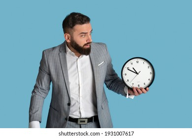 Scared office employee with clock missing deadline on blue studio background. Millennial bearded businessman having time management problem, being late for important meeting