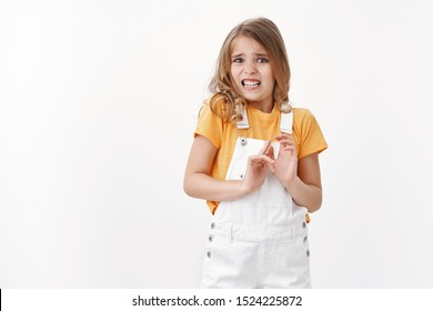 Scared reluctant blond little girl with blue eyes express disgust and aversion, cringe from awful smell, raise hands block refusal, rejecting disgusting thing, stand white background grimacing