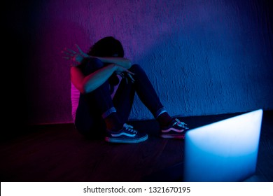 scared and sad female teenager with computer laptop suffering cyberbullying and harassment being online abused by stalker or gossip feeling desperate and humiliated in cyber bullying