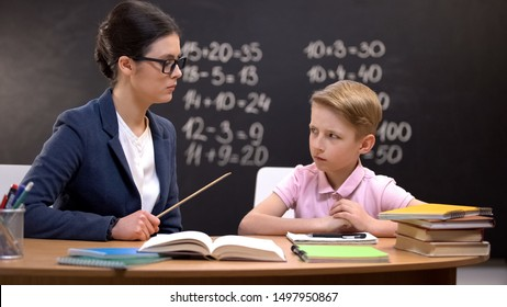 Scared schoolboy cautiously looking at strict teacher with pointer, education