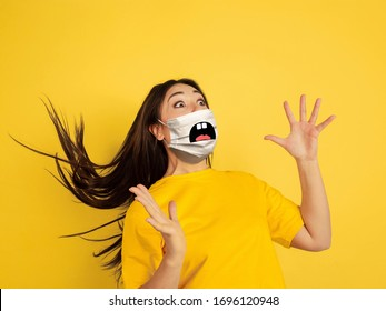 Scared screaming. Portrait of young caucasian woman with emotion on her protective face mask isolated on studio background. Beautiful female model. Human emotions, facial expression, sales, ad concept