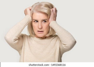 Scared senior gray-haired woman isolated, grey studio background look aside feel frightened terrified, mature aged lady freaking out face fear fence herself from threat, need support. Emotions concept