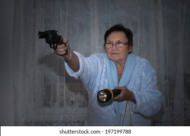 Scared senior woman aiming a gun and torch.