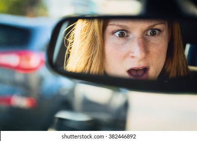 Scared or shocked female driver in a car - reflection in the rear view mirror.