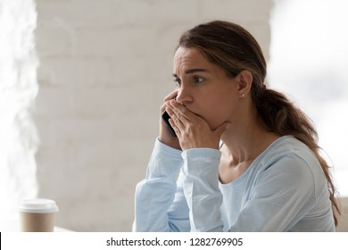 Scared shocked woman talking on phone, receiving bad news, having bad unpleasant conversation with friend or client, solving problem, sad disappointed businesswoman using smartphone
