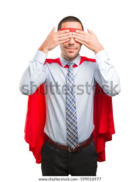 Scared super businessman covering his eyes