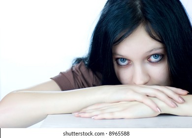 Scared teenage girl sitting near the table looking at you isolated on white