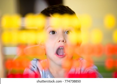 Scared toddler boy looking at abacus at home. Refusing to count. Attention deficit disorder