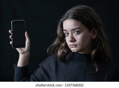 Scared upset girl bullied online suffering harassment crying feeling desperate and intimidated. Child victim of cyberbullying, stalker, social media and dangers of the Internet. Dramatic dark light.