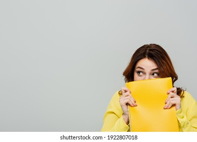 scared woman looking away while obscuring face with notebook isolated on grey