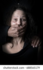 Scared woman with man's hand covering her mouth, victim of domestic violence