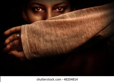 Scared woman protecting herself with her arm, on black background
