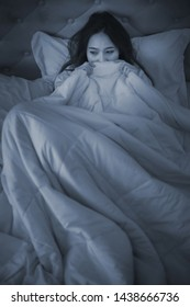 Scared woman pulling the blanket over her head at night time.