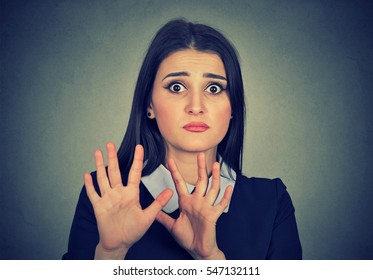 scared woman raising hands up afraid to be attacked avoiding unpleasant situation isolated on gray background
