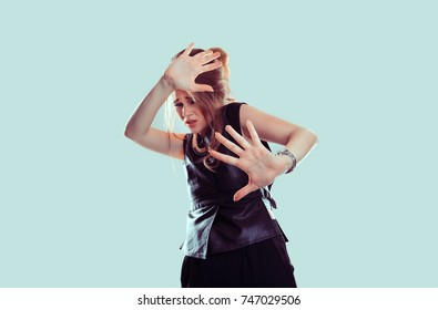 scared woman raising hands up in defense afraid about to be attacked or avoiding unpleasant situation, isolated on light blue background. Negative human emotion facial expression feeling