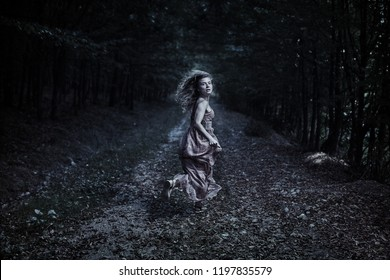Scared woman running through the forest