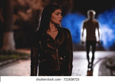 The scared woman stand on a dark street on a background of the man. night time