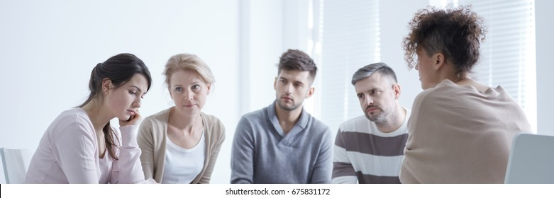 Scared woman suffering from anxiety disorder during group therapy