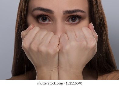 Scared woman. Terrified young woman covering mouth with hands and looking at camera while isolated on grey