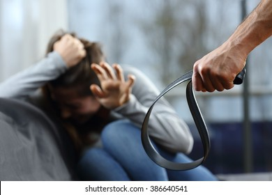 Scared woman threated with a belt by her husband at home with a window in the background in a dark day