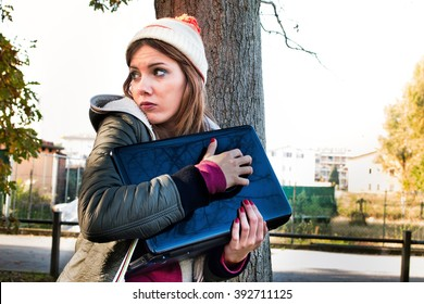 scared woman trying to protect her laptop pc and data looking helpless and vulnerable - privacy and identity theft concept - custom color tones and contrast effects added to add drama