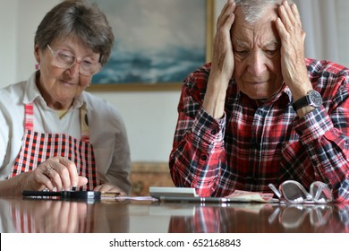 Scared and worried senior couple discussing and counting money from retirement, little savings, filling checks and control finance. Senior activities, retirement and old age concept.