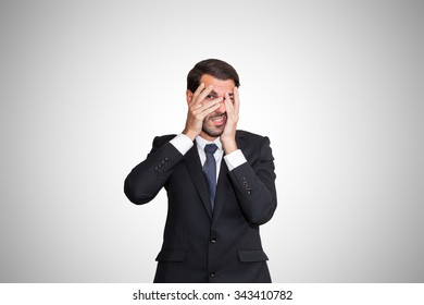 Scared young business man partially hiding his eyes.