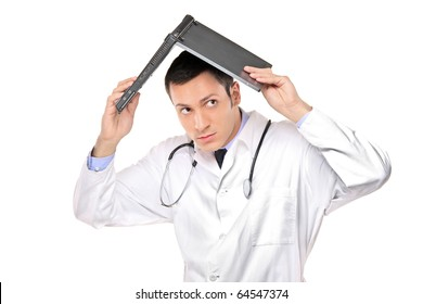 A scared young doctor covering his head with an open laptop isolated on white background